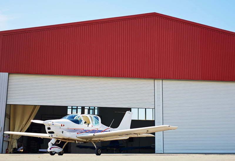 Prefabricated Steel Airplane Hangar Building with Airplane in front and Hangar door is open.
