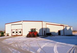 Prefab steel framed farm building with sliding steel door for equipment storage