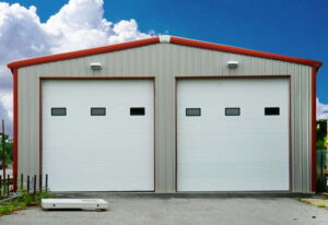 Exterior of a pre engineered steel workshop and garage storage building with double garage doors, white steel cladding, and red steel trim