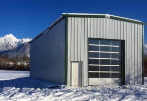 Exterior of a pre engineered steel workshop and garage with garage door, fox grey steel cladding, and burnished slate steel trim