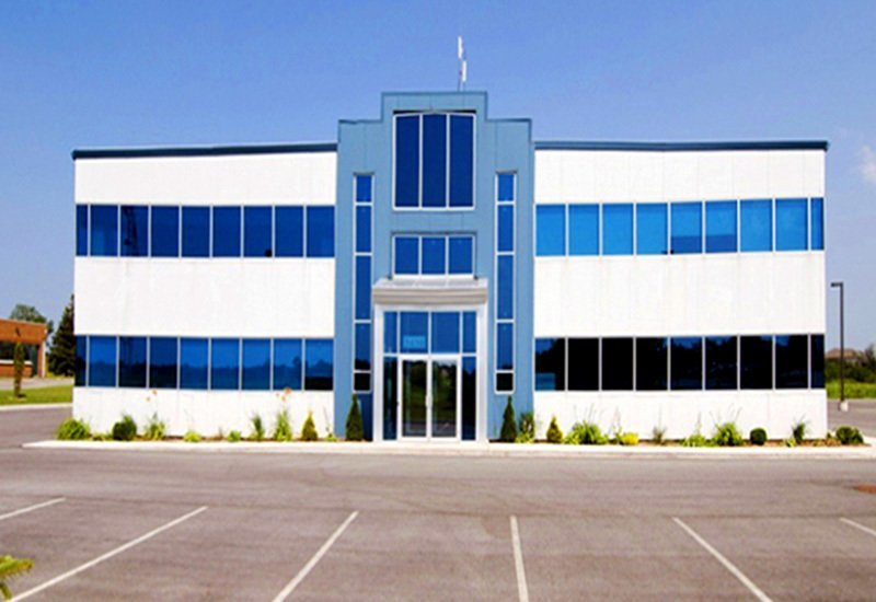 Exterior of a prefab steel office building with mezzanine, custom glass windows, and grand door entrance
