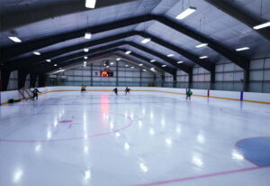 Interior image showing hockey players skating in a steel prefab sporting arena