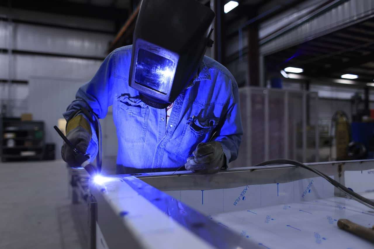 A welder constructing the components of a DIY steel building kit